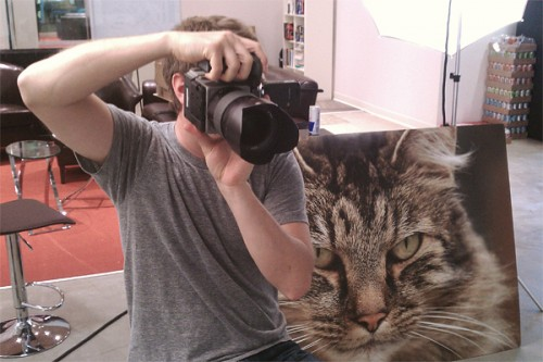 Photographer John Keatley helping his subject feel more comfortable with a giant cat face.