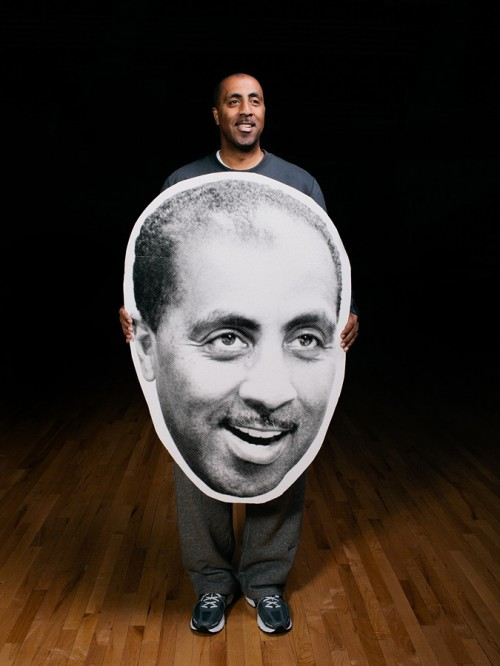 UW men's basketball coach Lorenzo Romar holding a giant picture of his face.  Photo by John Keatley.